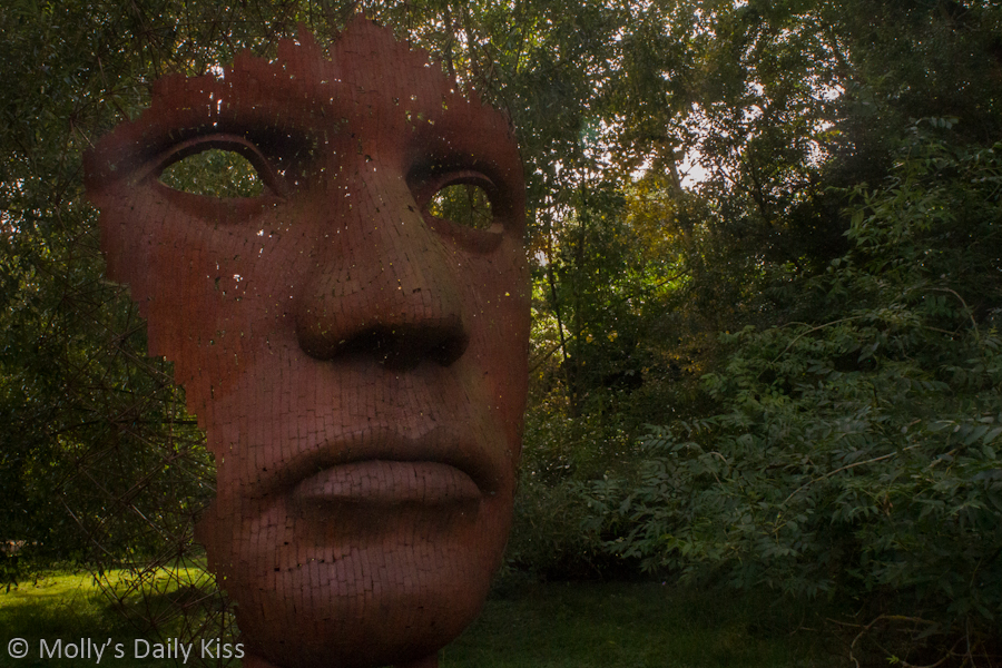 Face sculpure with empty eyes, notice