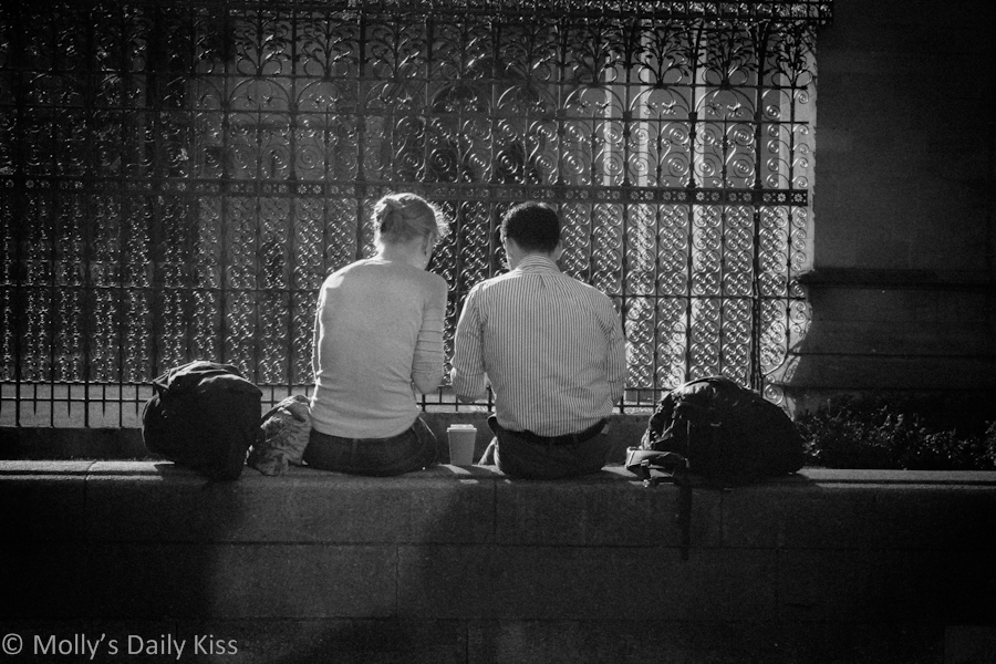 A couple sitting together on a wall