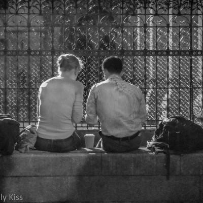Couple sitting on brick wall in sunshine