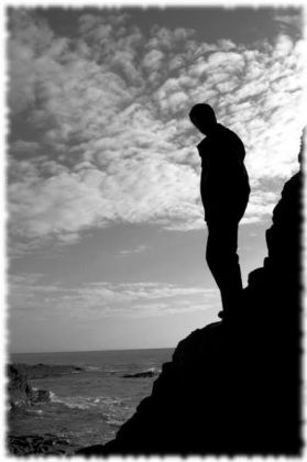 Silhouette of man stanind on rocks