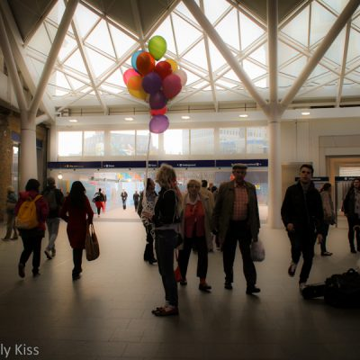 Woman at train station holding lots of coloured balloons