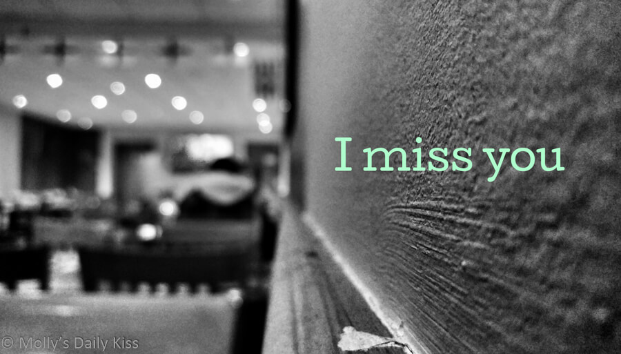 Man sitting alone in cafe on the wall it says I miss you