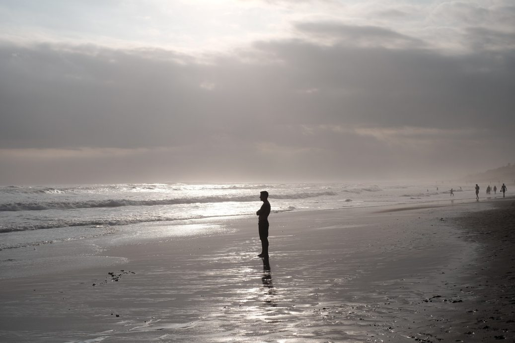 Man standing on the beach looking out to sea